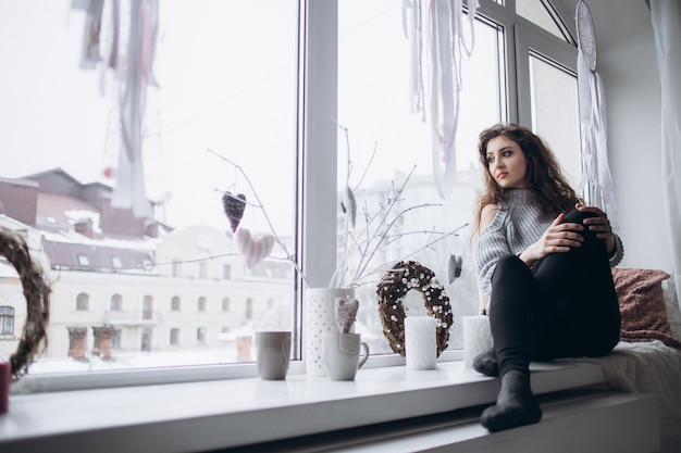 Stylowa dziewczyna siedząca na parapecie