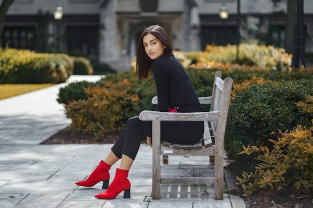Stylowa dziewczyna siedzi na ławce w szkole
