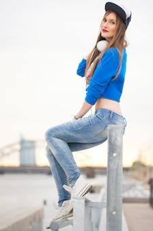 Stylowa dziewczyna siedzi na poręczy