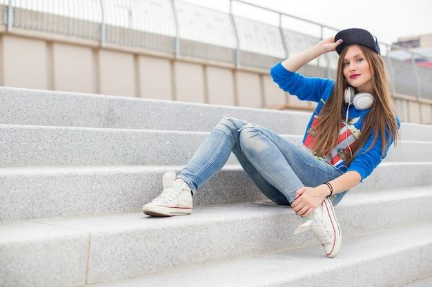 Stylowa dziewczyna siedzi na schodach