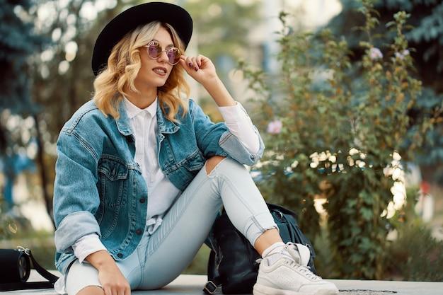 Stylowa dziewczyna spędzała czas w mieście siedząc przy nowoczesnym szklanym bu