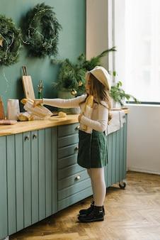 Stylowa dziewczyna stawia na boże narodzenie bagietki kuchenne na stole