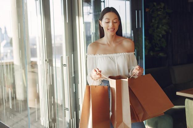 Stylowa dziewczyna stoi w kawiarni z torby na zakupy
