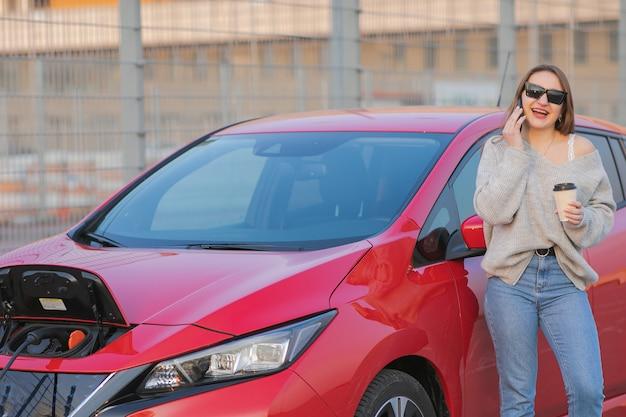 Stylowa dziewczyna stoi z telefonem w pobliżu swojego czerwonego samochodu elektrycznego i czeka, aż pojazd się naładuje. podłączanie wtyczki ładowarki samochodu elektrycznego.
