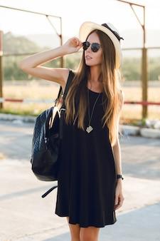 Stylowa dziewczyna stojąca w pobliżu drogi na sobie krótką czarną sukienkę, słomkowy kapelusz, czarne okulary i czarny plecak. uśmiecha się w ciepłych promieniach zachodzącego słońca. dotyka ręką okularów przeciwsłonecznych