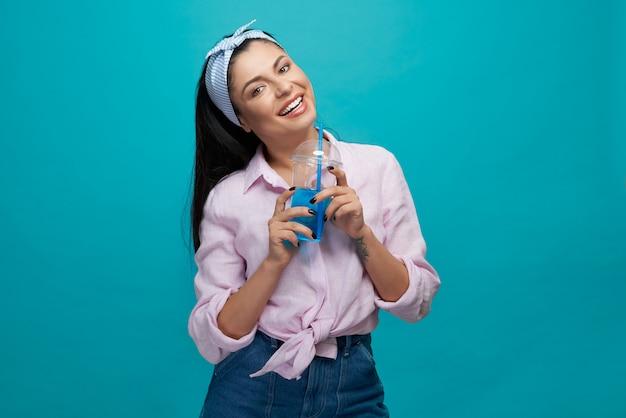 Stylowa dziewczyna trzyma plastikowy kubek z gazowanym napojem.