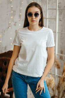 Stylowa dziewczyna ubrana w białą koszulkę i okulary przeciwsłoneczne, pozowanie w studio