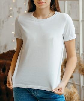 Stylowa dziewczyna ubrana w białą koszulkę pozowanie w studio