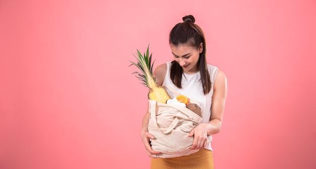 Stylowa dziewczyna uśmiechając się i trzymając eko torbę z egzotycznymi owocami