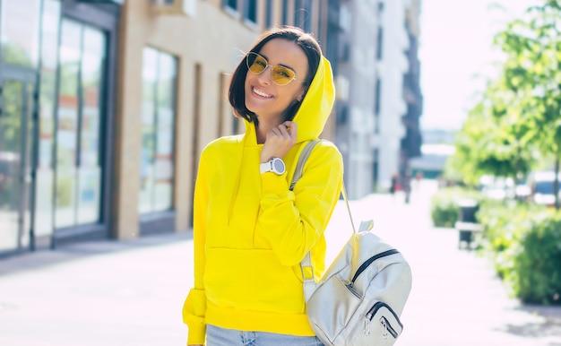Stylowa dziewczyna. uśmiechnięta dziewczyna na ulicy, w żółtych okularach, ze smartwatchem na dłoni, srebrnym plecakiem na ramieniu i kapturem na głowie.
