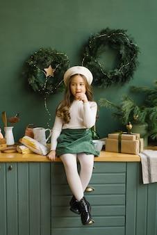 Stylowa dziewczyna w berecie siedząca w kuchni, udekorowana na boże narodzenie i nowy rok i jedząca bagietkę