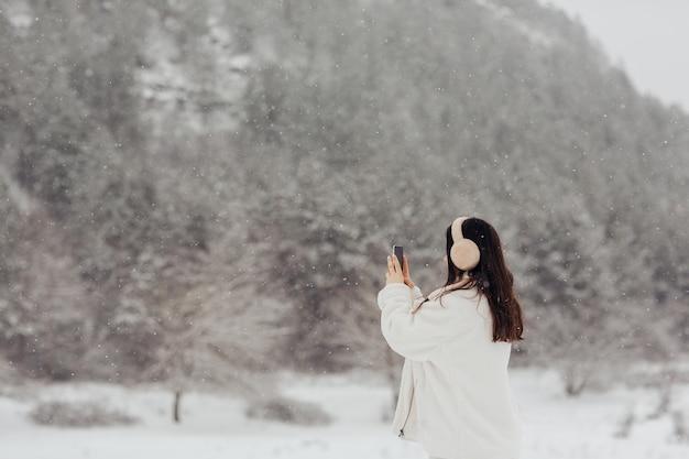 Stylowa dziewczyna w białych zimowych ubraniach i puszystych słuchawkach robi zdjęcie w pięknym krajobrazie w górach podczas opadów śniegu.