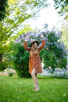 Stylowa dziewczyna w brązowym kapeluszu i lekkiej sukience na tle bzu bujnych krzewów. młoda kobieta z uśmiechem na twarzy w słoneczny letni dzień spaceruje po parku