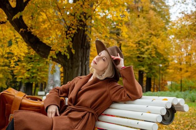 Stylowa dziewczyna w brązowym płaszczu z walizką siedzi na ławce w jesiennym parku