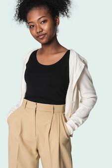 Stylowa dziewczyna w czarnej koszulce z beżowym sweterkiem i spodniami z sesji mody młodzieżowej