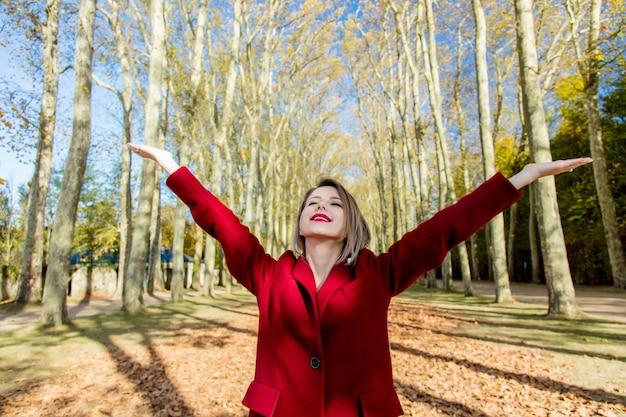 Stylowa dziewczyna w czerwonym płaszczu w parku w wersalu