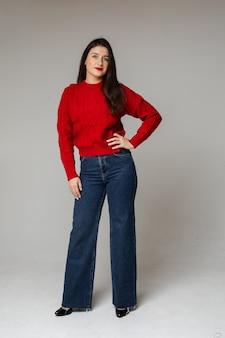 Stylowa dziewczyna w czerwonym swetrze i dżinsach.