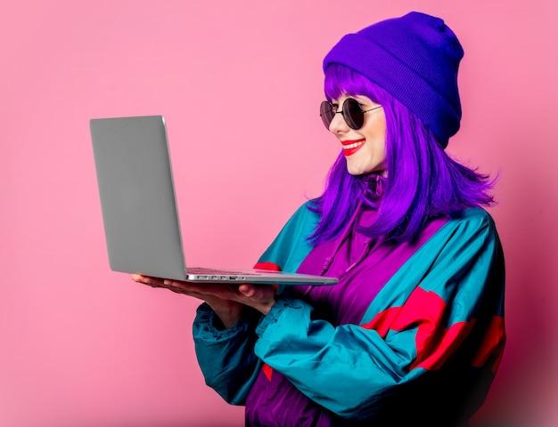 Stylowa dziewczyna w dresie trzyma laptopa na różowej ścianie