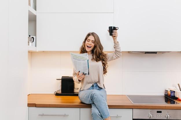 Stylowa dziewczyna w dżinsach podnosząc filiżankę herbaty i śmiejąc się