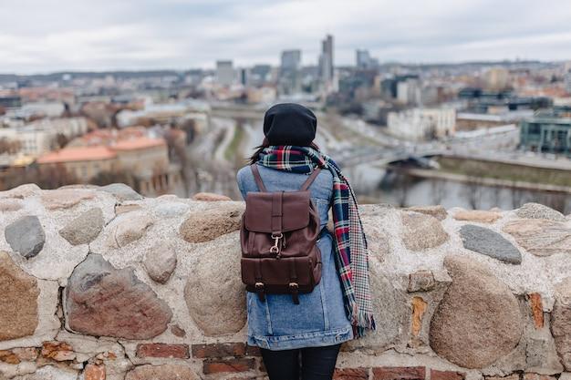 Stylowa dziewczyna w dżinsowej kurtce chodzi przy vilnius tłem