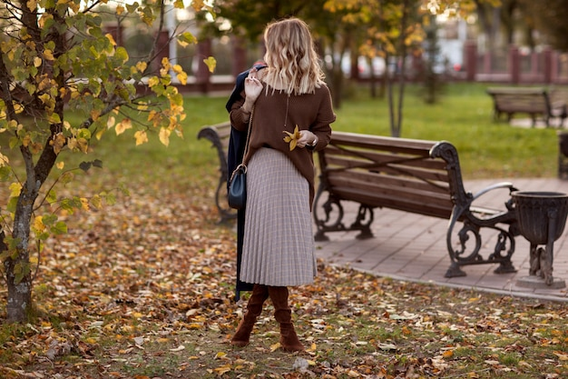 Stylowa dziewczyna w jesiennym parku w brązowym swetrze i spódnicy w kratę.
