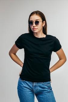 Stylowa dziewczyna w okularach na sobie czarną koszulkę, pozowanie na szarej ścianie