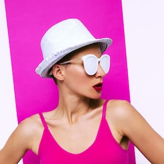 Stylowa dziewczyna w okularach przeciwsłonecznych i kapeluszu. minimalistyczna moda plażowa pop-artu