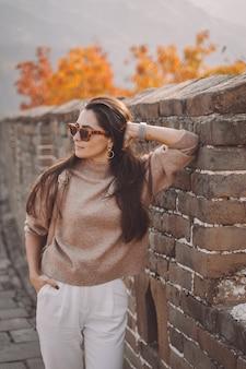 Stylowa dziewczyna w okularach przeciwsłonecznych odwiedzająca wielki mur chiński
