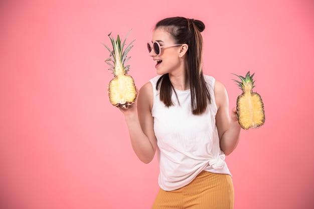 Stylowa dziewczyna w okularach uśmiecha się i trzyma owoce na różowej ścianie. koncepcja wakacji letnich.
