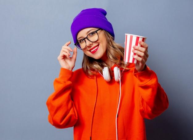 Stylowa dziewczyna w pomarańczowej bluzie z kapturem i fioletowym kapeluszu z filiżanką na szarej ścianie