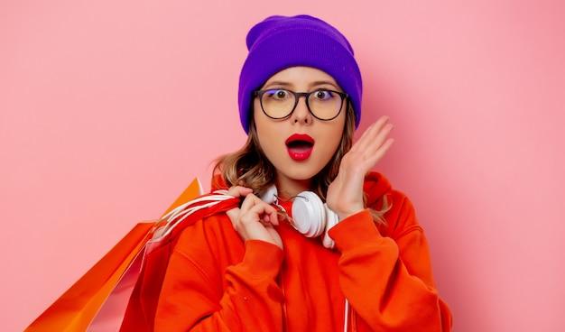 Stylowa dziewczyna w pomarańczowej bluzie z kapturem i fioletowym kapeluszu z torbami na zakupy na różowej ścianie