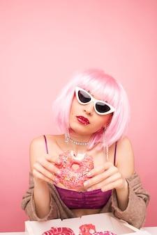 Stylowa dziewczyna w różowej peruce je pyszne pączki na różowo