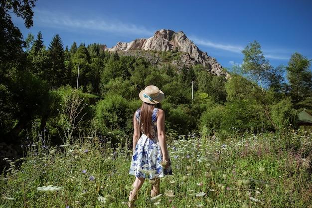 Stylowa dziewczyna w słomkowym kapeluszu podróżująca po słonecznych górach.