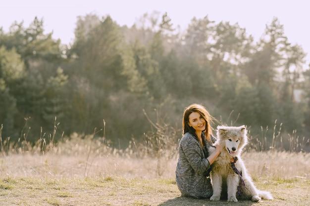 Stylowa dziewczyna w słonecznym polu z psem