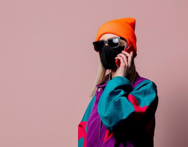 Stylowa dziewczyna w sportowym kostiumie z lat 80. i masce na twarz za pomocą telefonu komórkowego na różowej ścianie