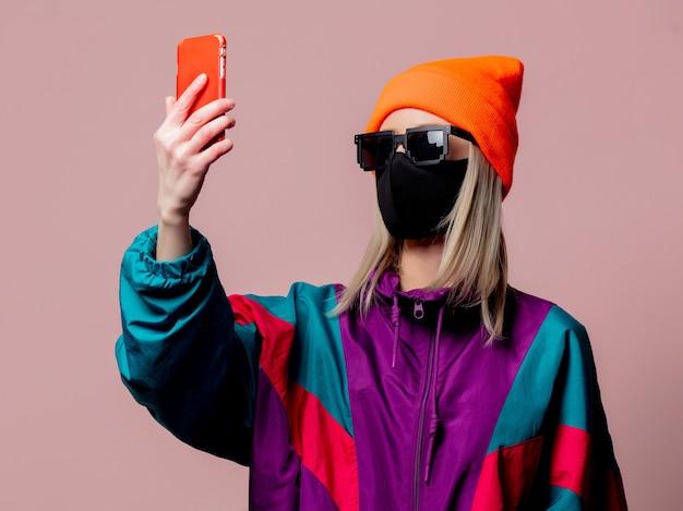 Stylowa Dziewczyna W Sportowym Kostiumie Z Lat 80. I Masce Na Twarz Za Pomocą Telefonu Komórkowego Na Różowej ścianie Premium Zdjęcia