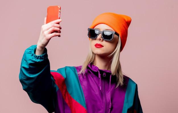 Stylowa dziewczyna w sportowym kostiumie z lat 80. i okularach przeciwsłonecznych trzyma telefon komórkowy na różowej ścianie