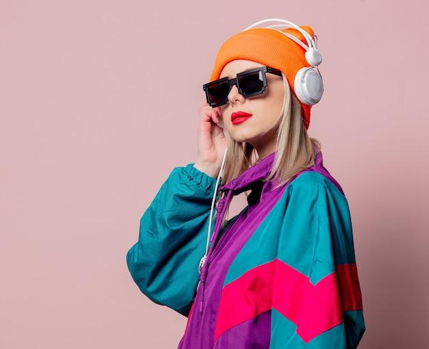 Stylowa dziewczyna w sportowym kostiumie z lat 80. i okularach przeciwsłonecznych ze słuchawkami na różowej ścianie