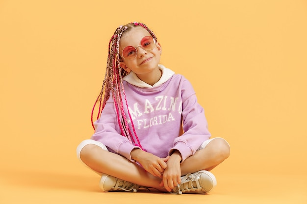 Stylowa dziewczyna w zaokrąglonych okularach z różowymi dredami pozowanie na żółtym tle