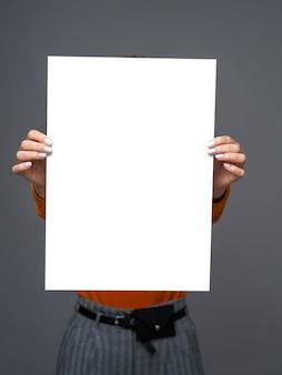 Stylowa dziewczyna z dużym arkuszem papieru w dłoniach
