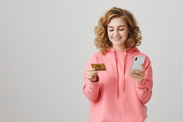 Stylowa dziewczyna z kręconymi włosami robi zakupy online za pomocą karty kredytowej i smartfona