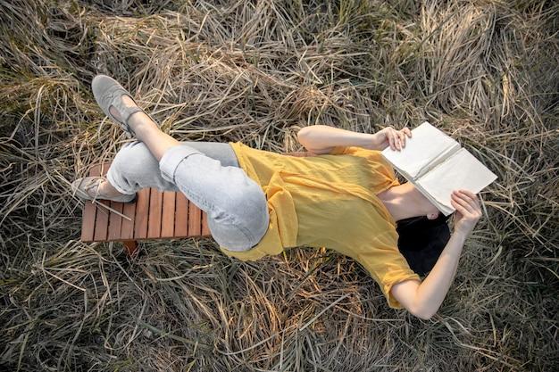 Stylowa dziewczyna z książką w dłoniach leży wśród trawy na łonie natury.