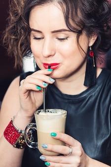 Stylowa dziewczyna z ręcznie robioną biżuterią pije cappuccino.