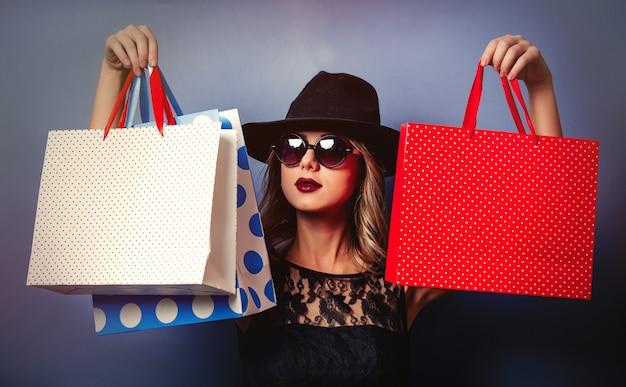 Stylowa dziewczyna z torba na zakupy na szarości ścianie