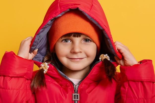 Stylowa dziewczynka 4-5 lat ubrana w jesienną kurtkę i pomarańczową czapkę