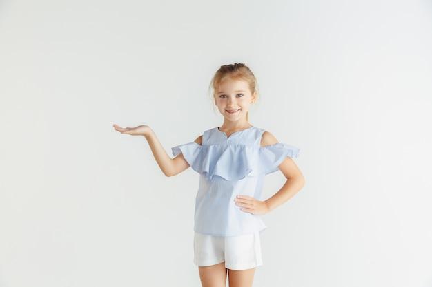 Stylowa dziewczynka uśmiechający się pozowanie w ubranie na białym tle na tle białego studia. kaukaski blond modelka. ludzkie emocje, wyraz twarzy, dzieciństwo. pokazuje puste miejsce.