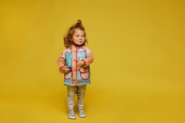 Stylowa dziewczynka w modny płaszcz przeciwdeszczowy na białym tle na żółtym tle.