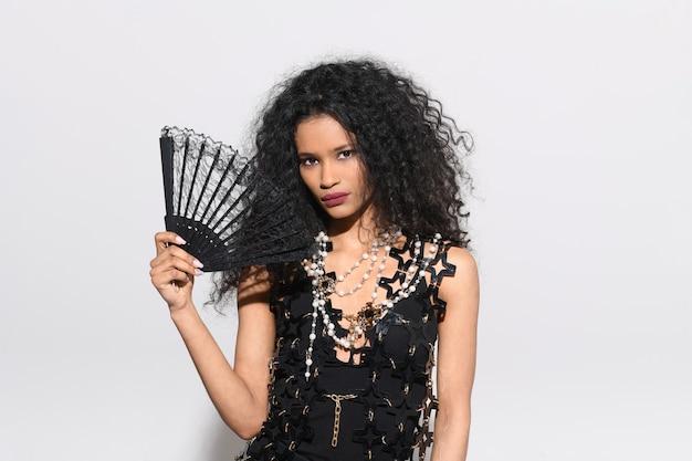 Stylowa, elegancka dziewczyna z dominikany w czarnej designerskiej sukience trzymająca składany wachlarz z czarnej koronki i ubrana w naszyjnik z koralików