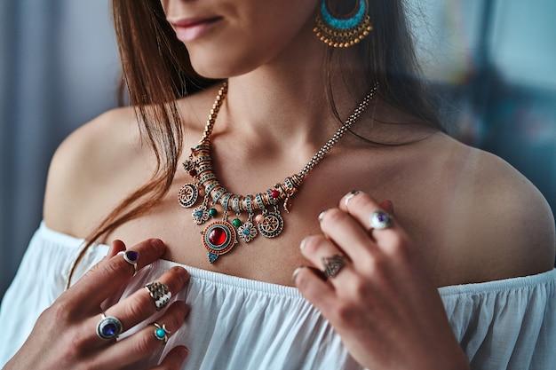 Stylowa elegancka kobieta boho ubrana w białą bluzkę ze złotym naszyjnikiem i srebrnymi pierścieniami z kamieniem. modny cygański cygański indyjski strój z detalami jubilerskimi
