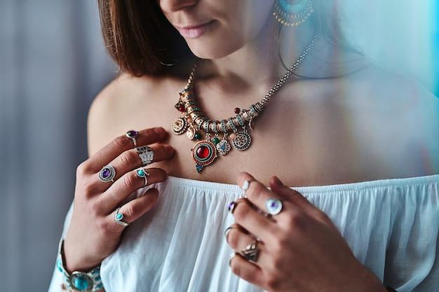 Stylowa elegancka kobieta w stylu boho ubrana w białą bluzkę ze złotym dużym naszyjnikiem i srebrnymi pierścieniami z kamieniem. modny cygański cygański indyjski strój z detalami z biżuterii